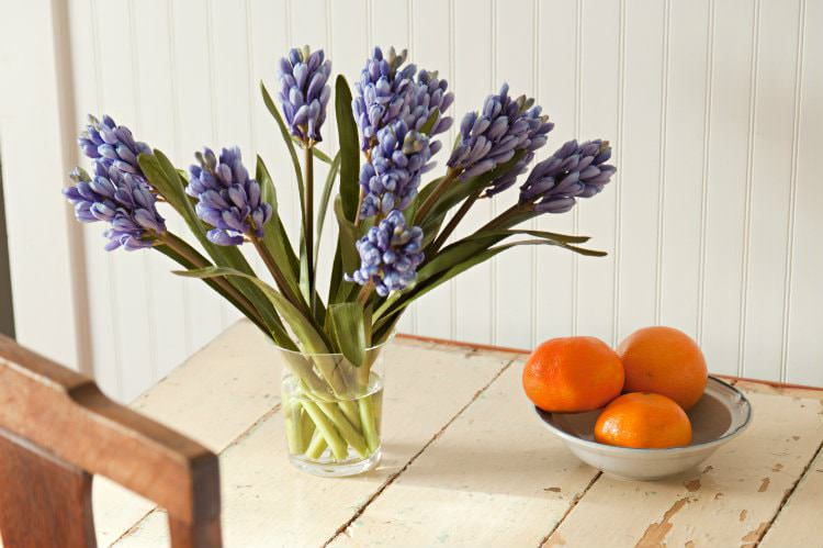 Rustic wood table topped with fresh purple flowers and bowl of fresh oranges