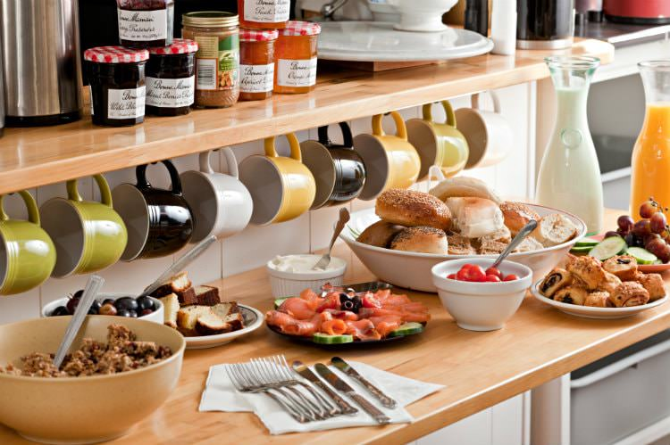 Butcher block counter topped with breakfast foods under a row of colorful mugs hanging from a wood shelf