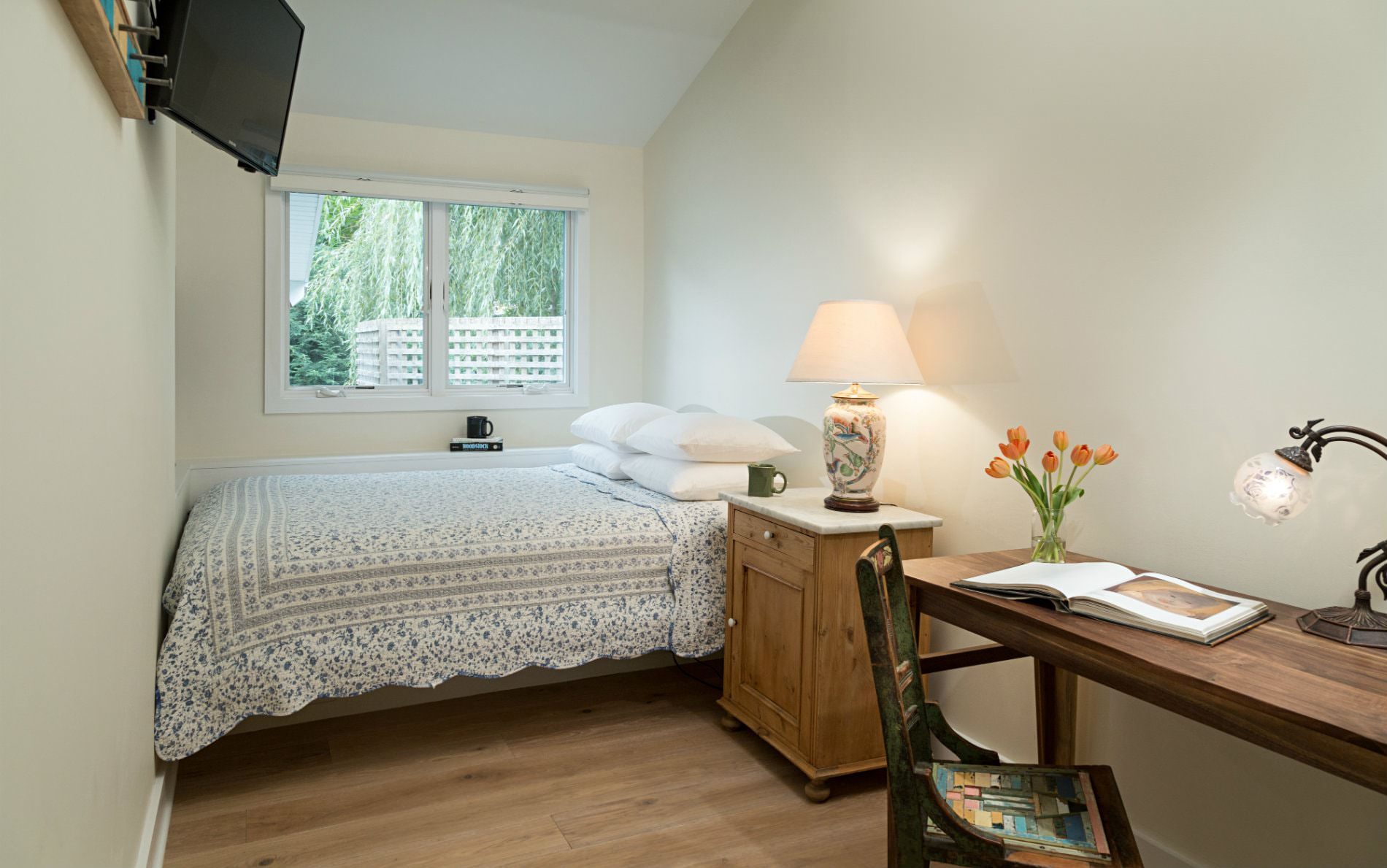 White vaulted room with double window, wood floor, bed with nightstand and lamp, and writing desk with lamp and chair