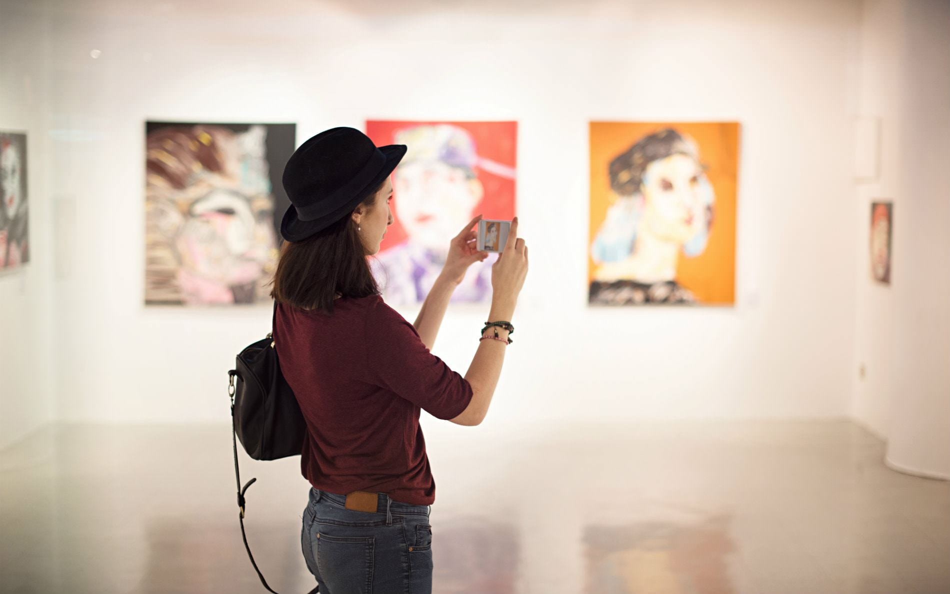 Brown haired woman with black hat, red shirt, and jeans taking a photograph of art hanging on white walls