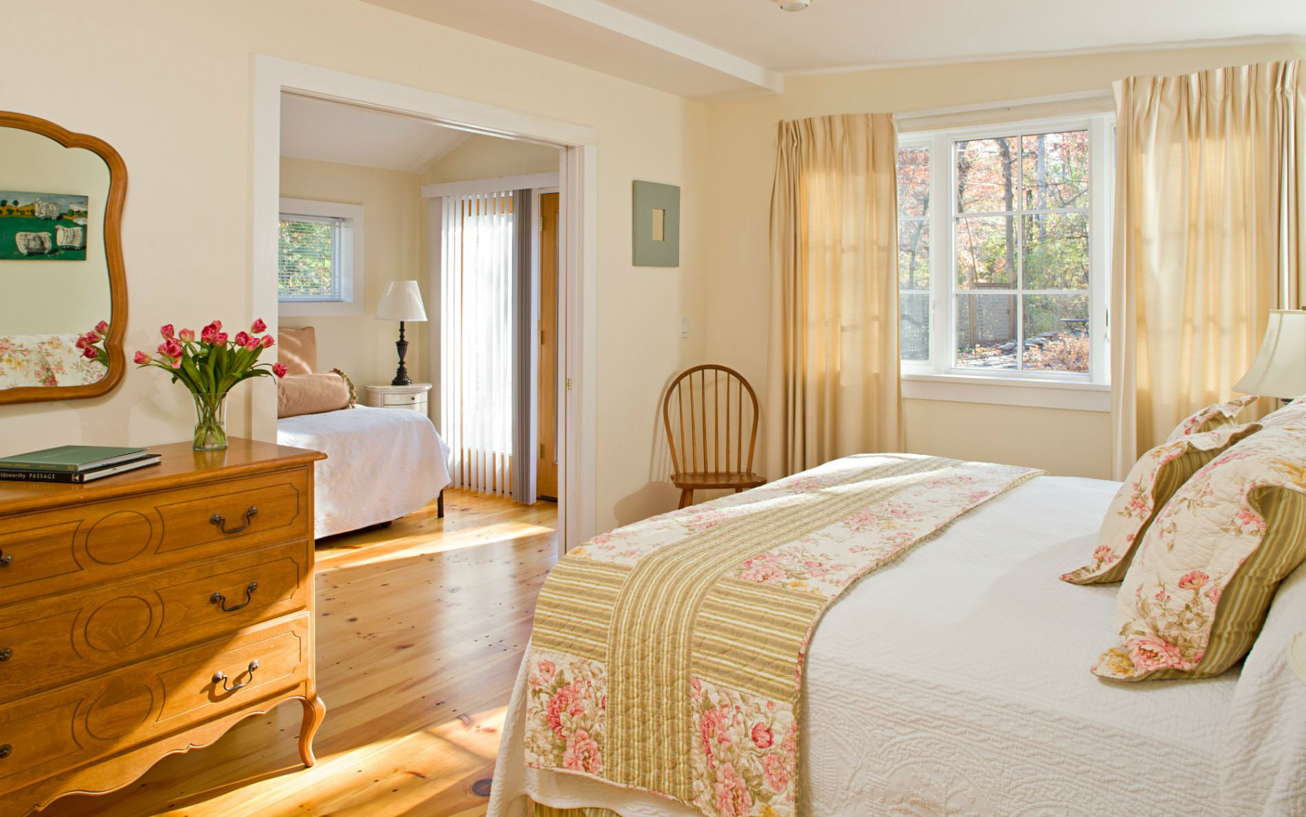 Warm and cozy beige and white adjoining rooms with wood floors, lots of natural light, and white covered beds