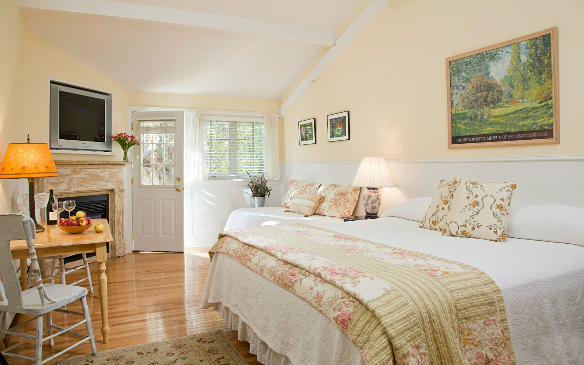 Beige and white vaulted room with wood floors, flat screen tv, fireplace, wooden table and chairs and white covered bed