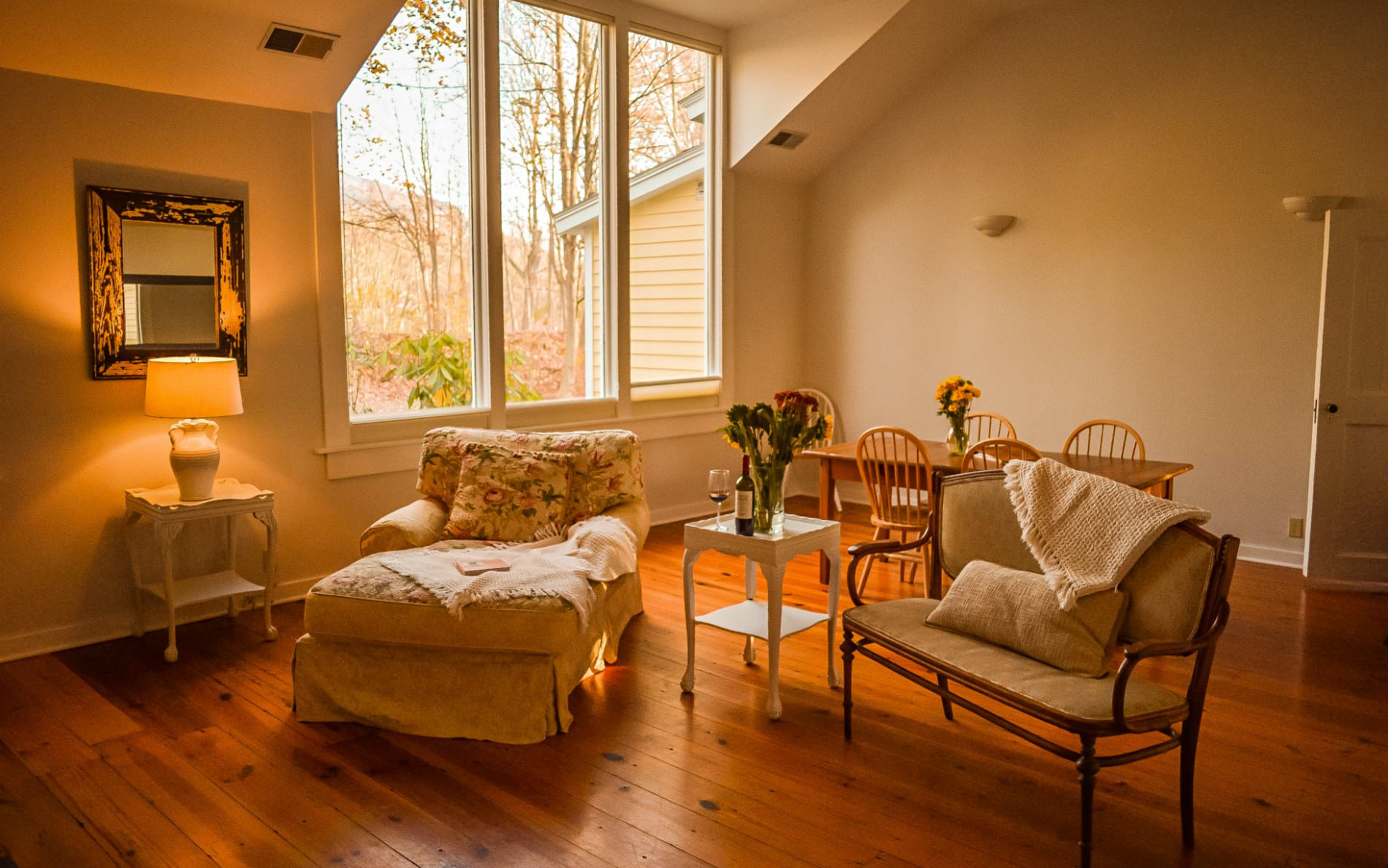 Cozy beige vaulted room with wood floors, large triple window, wood dining table and chairs, and sitting area