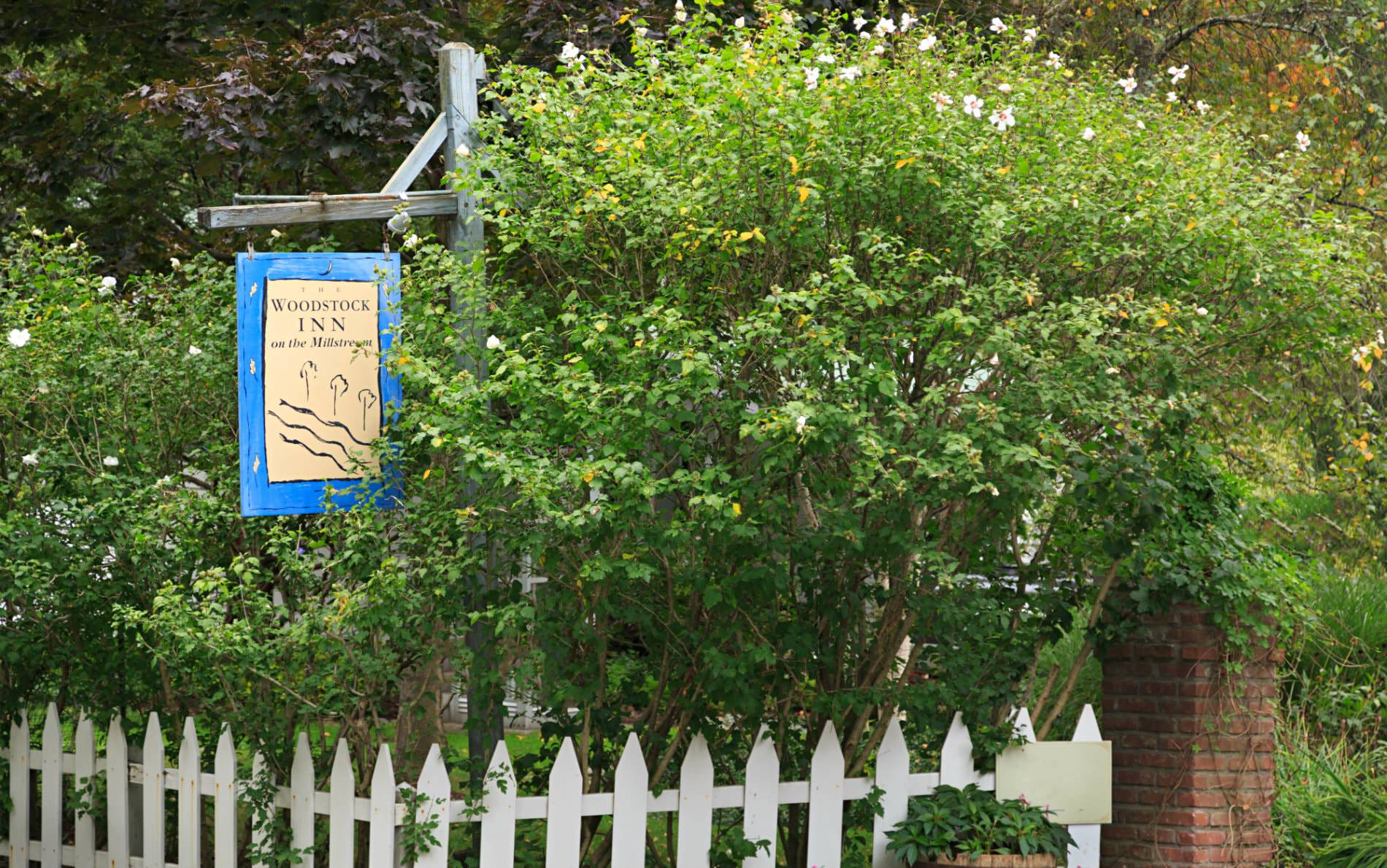 Beige and blue Woodstock Inn sign hanging from rustic wood post over a white picket fence surrounded by greenery