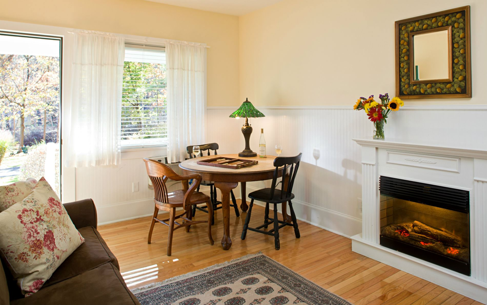 Beige and white room with wood floors, glass door and window, fireplace, and round table and chairs