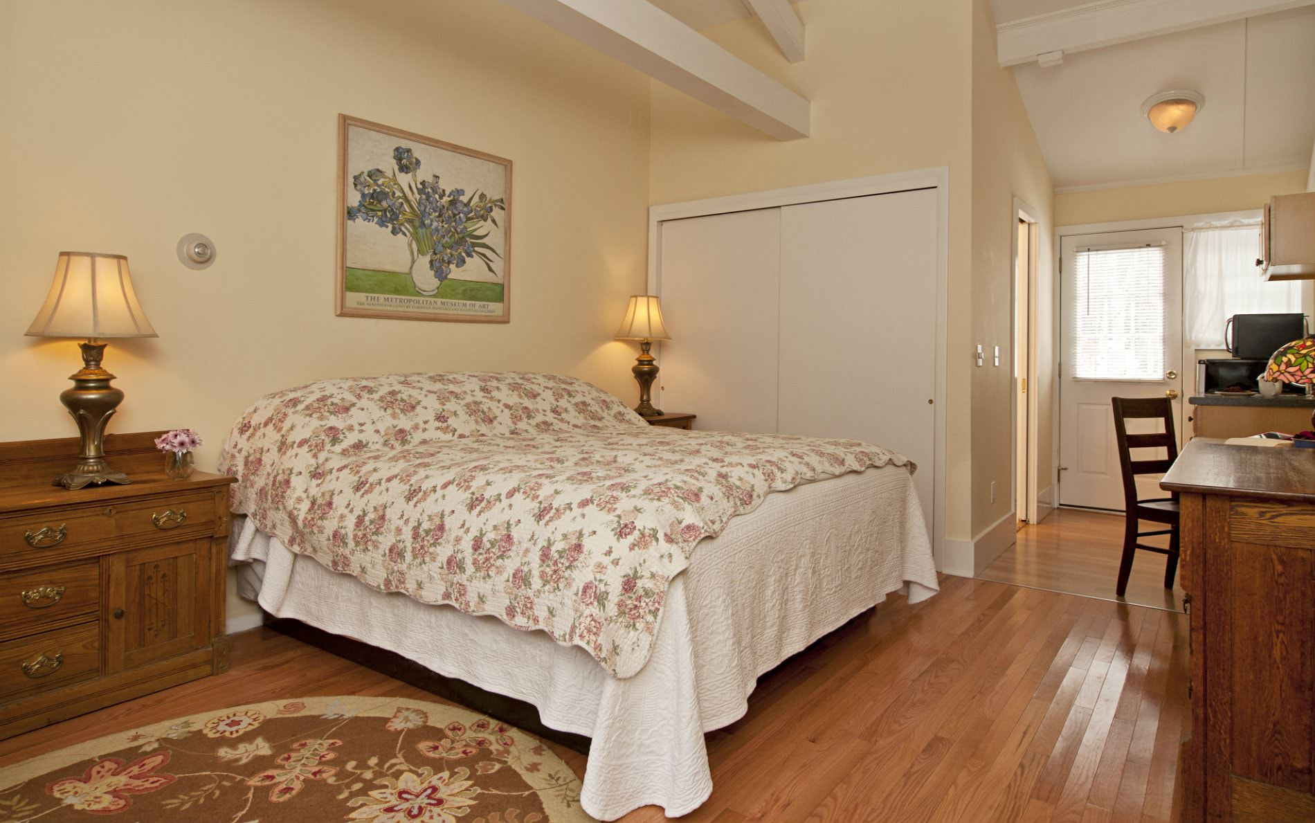 Beige room with dark carpet, white covered bed, dresser with mirror, desk and chair, and side chair with round table