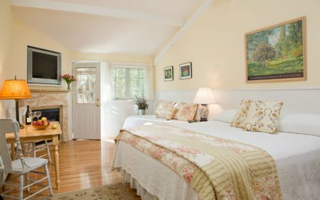 Beige vaulted room with wood floors, flat screen tv, fireplace, white covered bed and small wood table and chairs