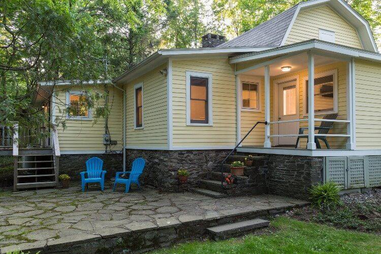 A bluestone patio wraps around a porch that has a door.
