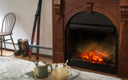a tray on a bed with two mugs of hot cocoa, a fireplace in teh background with orange flames and a pair cross country skis leaning against the white wall.