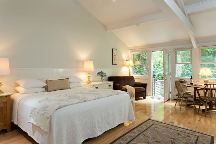 White vaulted room with wood floors, several windows, glass door, white covered bed, love seat, and table and chairs