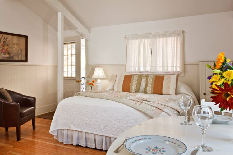 White vaulted room with wood floor, white covered bed, round white table with fresh flowers, and leather club chair