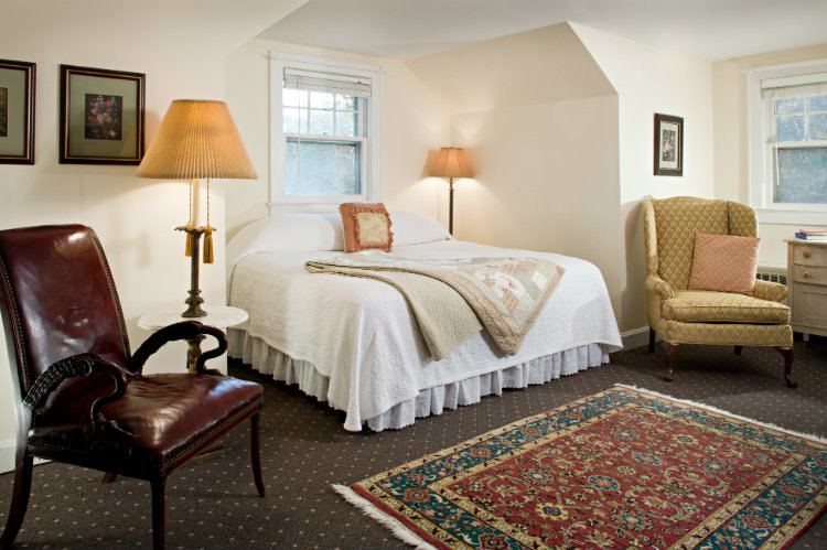 Beige room with dark carpet, colorful rug, white covered bed, one upholstered and one leather side chair, and two windows