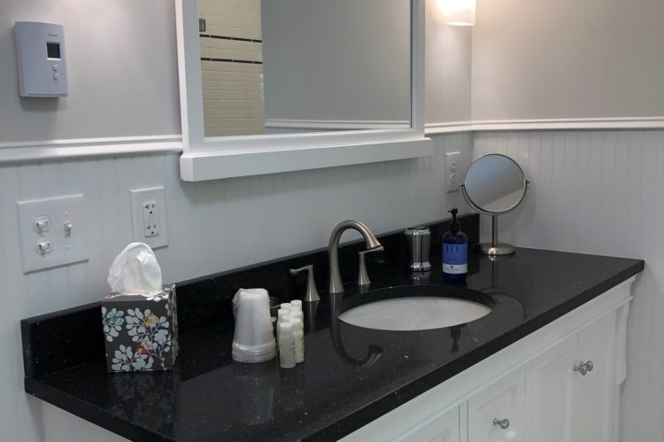 The bathroom includes a black vanity with a white sink.