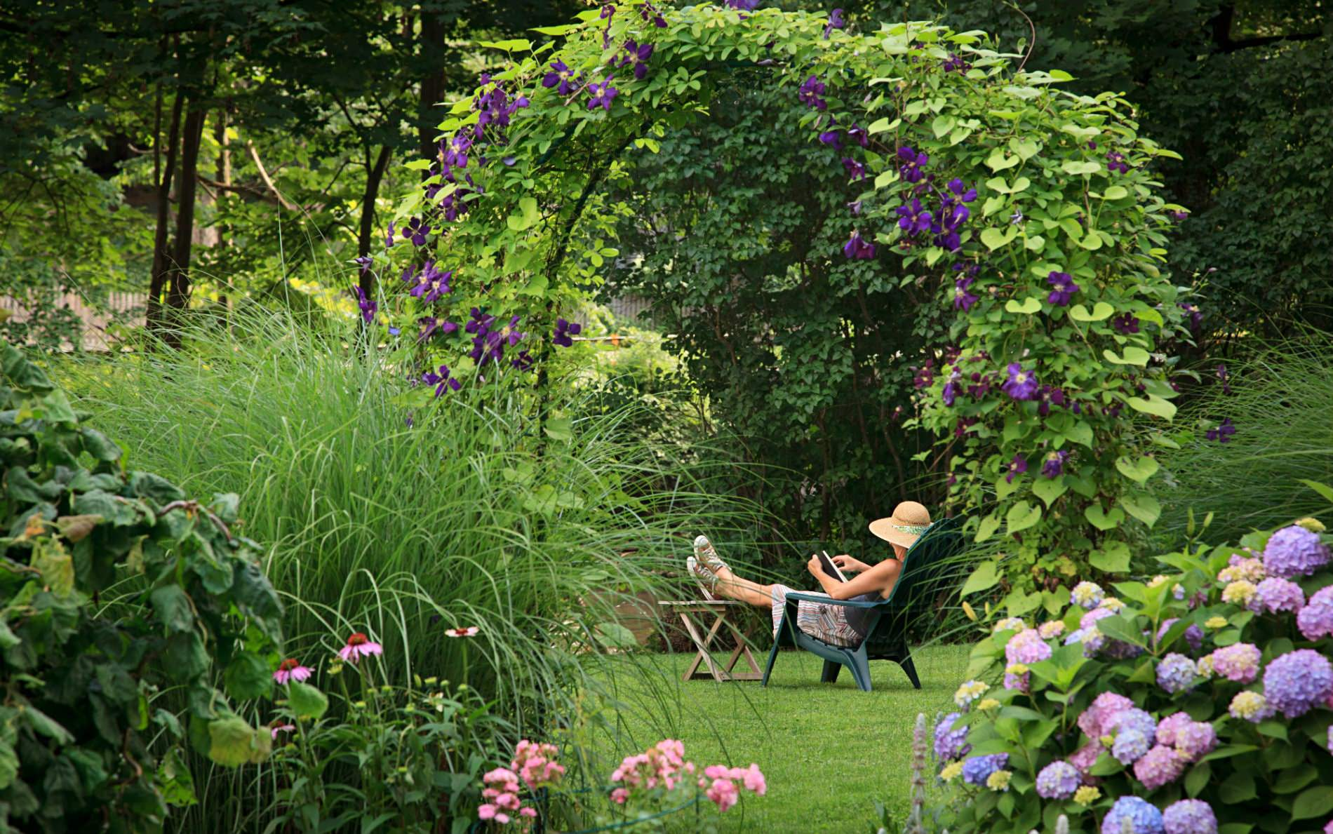 Woman relaxing in an Adirondack chair surrounded by green grass and lush green shrubs, flowers and trees