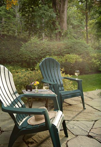 Flagstone patio with two green Adirondack chairs and table surrounded by green grass, shrubs and trees