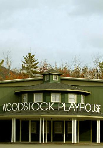 Exterior view of green and white Woodstock Playhouse surrounded by cloudy skies and autumn trees