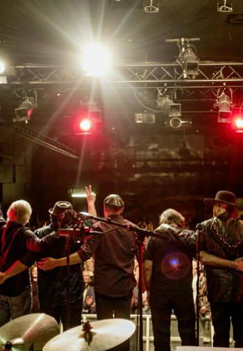 Backstage view of country band during an encore before an audience with white and red lights overhead