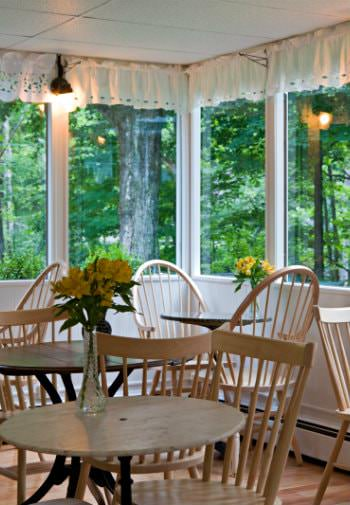 Wood tables and chairs topped with fresh yellow flowers surrounded by windows overlooking lush greenery