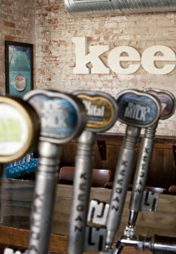 Close-up view of beer tap handles surrounded by white washed brick walls and dark wood tables and chairs