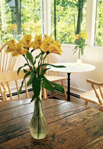 Wooden tables and chairs topped with glass vases of yellow flowers surrounded by windows overlooking green trees
