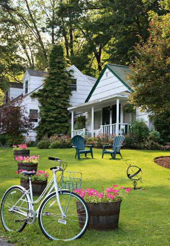 Adirondack chairs, round tubs of pink flowers, and white bicycle on green lawn - tall trees and white cottages in background
